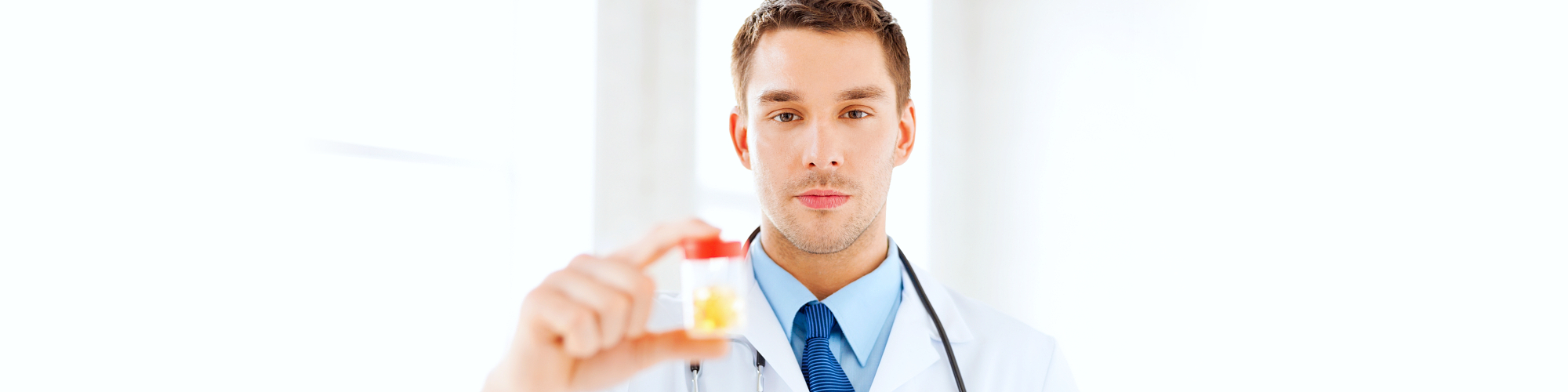 doctor looking at camera while holding medicine